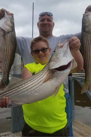 Father & Son Holding Stripers at Lake Texoma after trip with Wylie Guide Services