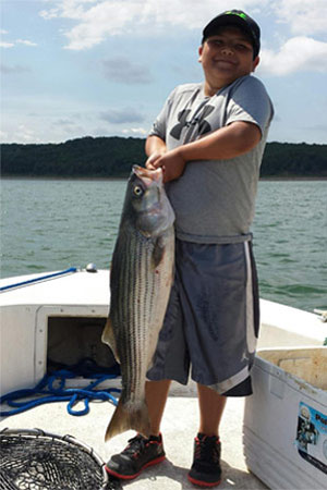 Kid holding striped bass at Lake Texoma after trip with Randy Wylie's Guide Services