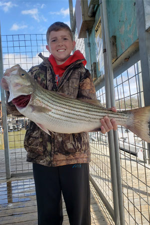 Kid holding striped bass at Lake Texoma after trip with with Wylie Guide Services