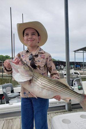 Kid holding striper at Lake Texoma after trip with Randy Wylie's Guide Services