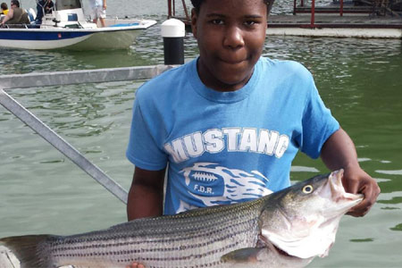 Kid holding striper at Lake Texoma after trip with Wylie Guide Services