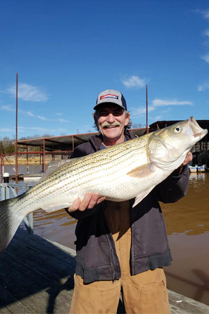 Man holding striper at Lake Texoma after trip with with Randy's Guide Service