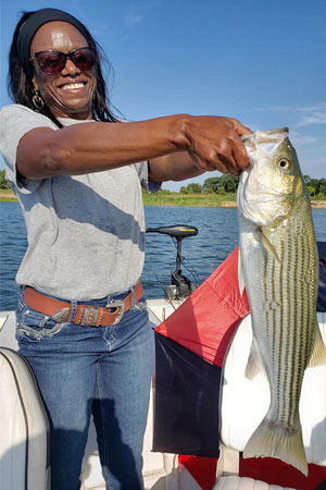 Woman holding striper at Lake Texoma after trip with with Wylie Guide Services